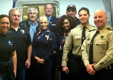 St. Bernard sheriff's deputies Capt. Ronnie Martin, at right, and next to him Carlo Cacioppo, with the fllight crew and other poice officers who flew back from New York after the funeral of a slain police officer.