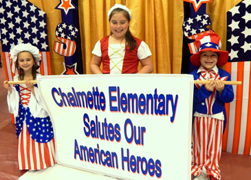 "Students, from left, Layla Serpas, Kylee Schallenberg and Nathan Schallenberg prepare to lead a procession with a sign singalling the theme of the Mardi Gras ball: ""Chalmette Elementary Salutes Our American Heroes.''"