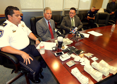 Maj. Chad Clark, Sheriff James Pohlmann and District Attorney Perry Nicosia discuss the large heroin seizure while sitting at a table displaying the drugs and money confiscated.