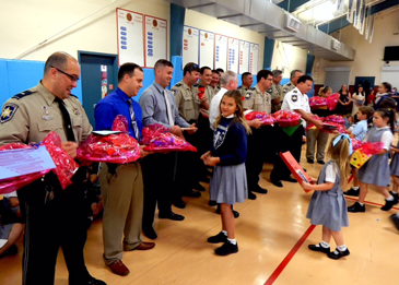 Prompt Succor School students present baskets of snacks to officers attending the event.