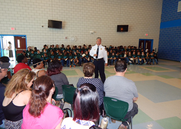 Sheriff Pohlmann talks to parents at Arabi Elementary, with graduating 5th-graders seated behind him.