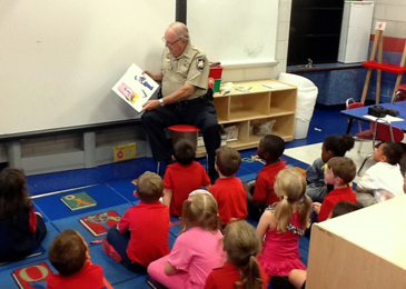 Dep. Sheriff Lt. Billy Cure reads to pre-schoolers at Gauthier Elementary School as part of their  Literacy Week celebration.