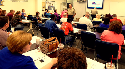 A large group of participants listen to Capt. Charles Borchers on the opening night of the Sheriff's Citizens Police Academy in 2014.