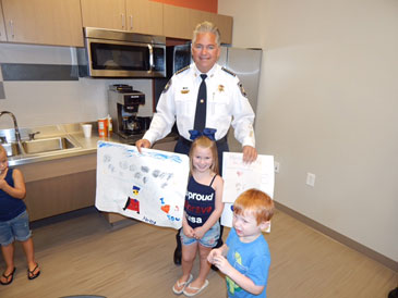 Sheriff Pohlmann holds a card made by children for an event to show support for law enforcement and in front are are two children who took part.