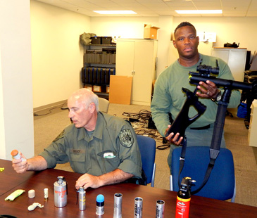 Lt. Ray Theriot, seated, discusses weapons used by the Sheriff's Office SWAT team to members of the current class of the Citizens Police Academy while Det. Sgt. Donald Johnson, standing, holds a gun used for firing gas canisters.