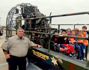 Cpl. Shane Lulei stands next to an airboat on which children are sitting.