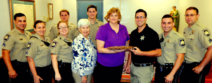 Two representatives from a chapter of the Daughters of the American Revolution brought cookies to St. Bernard Parish sheriff's deputies and fire fighters recently to thank them for the work they do. Aileen Alfortish of St. Bernard Parish is shown handing a platter of cookies to Lt. Justin Meyers at Parish Prison, and Carolyn Morris of Baton Rouge is next to her. They are surrounded by officers who work in the jail.