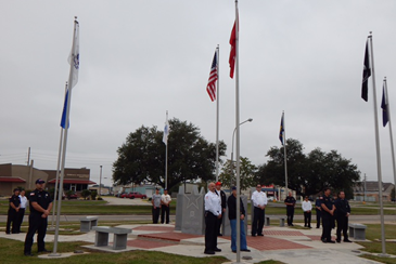 Flags are raised at the Veterans Monument near parish government.