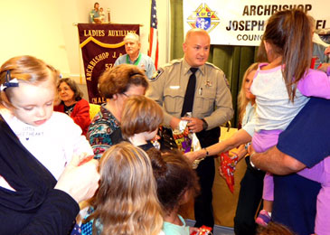 Dep.ustin Gould and Rhonda Serignet are shown handing out key chains from the Sheriff's Office and other items to children.