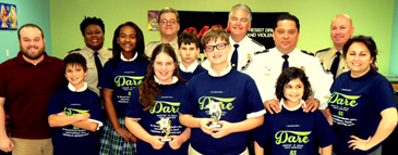 "D.A.R.E. essay winners and others in 5th-grade at Lynn Oaks are shown at the graduation. 1st-place winner Emma Gonzales and 2nd-place winner Andrew Nata, both holding trophies, are in front. Behind them are students Jon ""Nik"" Wilson, Maci Ross, D.J. Melerine and Keira-Raven Hood and Principal Kim Duplantier. In back are teacher Chris Wilder Jr., D.A.R.E. program coordinator Lt. Lisa Jackson, D.A.R.E. officer Sgt. Darrin Miller, Sheriff James Pohlmann, Maj. Chad Clark and Capt. Ronnie Martin."