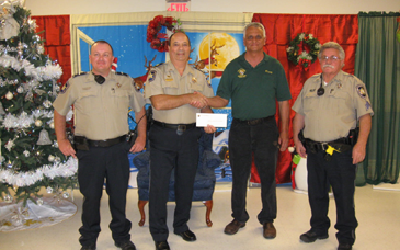 Capt. Charles Borchers, who coordinates the Reserve Division, accepts a check from Russell Serpas Sr., Grand Knight of Rummel Council 5747 of the Knights of Columbus in Chalmette in appreciation of events the reserves worked this year. At left are Reserve Division Lt. Tony Jeansonne and at right is Reserve Division Sgt. Albert Loar.