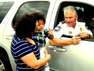 Sheriff James Pohlmann gives a special doubloon to a child during the Knights of Nemesis parade on Jan. 30.