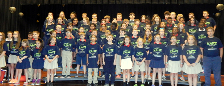 Gauthier students face parents and relatives to perform D.A.R.E. program songs.