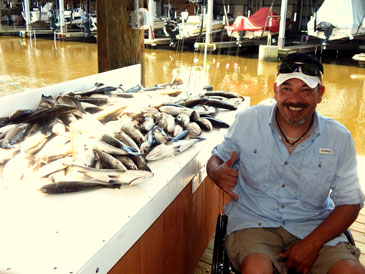 John Sanchez of San Antonio, one of the veterans involved, sits next to a table with a mess of fish caught on the fishing trip.