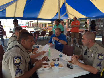 St. Bernard sheriff's deputies eat lunch under a tent at the Trumpet of Truth Ministry in Arabi.