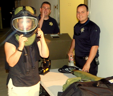 A participant in last year's Citizen's Police Academy tries on part of a Sheriff's Office bomb suit, during an equipment demonstration while in the background are bomb squad members Capt. Daniel Doucet and Sgt. Ryan Melerine.