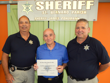 Hilton Preau, center, received an award for volunteering his time to help with the academy the last two years. At left is Capt. Charles Borchers and, at right, is Dep. Sheriff Eric Eilers.