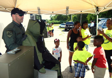 Sgt. Chris Scheeler of the Bomb Squad shows how heavy a bomb suit is.