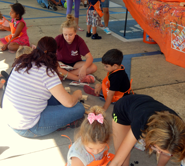 Children and parents work on activities under a tent at the Home Depot Kids Safety Day on Oct. 1.