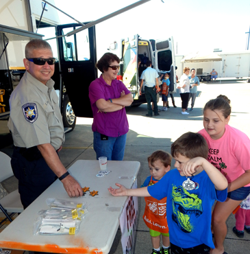 Logan Gremillion, in front, reaches for a Sheriff's Office Junior Deputy badge given out at the Kids Safety Day event. Behind him are Dean Gremillion and Sophia Menant. The  Sheriff's Deputy is Eric Eilers and next to him is his wife, Carol.