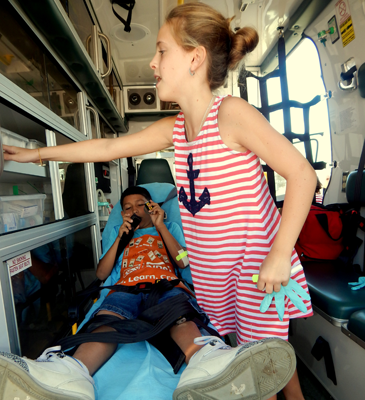 Bree Annah Rowell stands over patient Richard Quidroz, who lies on a gurney as they get to see inside an ambulance from Acadian Ambulance Service.