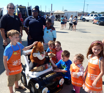 Children crowd in to play with the remote control car and figure of Daren the Lion, symbol of the Drug Abuse Resistance Education program, or D.A.R.E., taught in schools by the Sheriff's Office, In back are D.A.R.E. instructors Sgt. Darren Miller and Lt. Lisa Jackson, coordinator of the program.