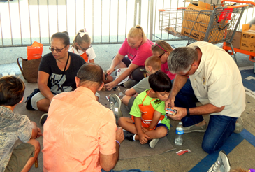Sheriff Pohlmann kneels to show something to a child, Antonio Spicuzza, at the Kids Safety Day event.