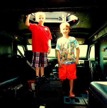 Two boys stand under the hatch in the Sheriff's Office S.W.A.T. truck.