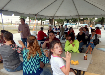 Families, including church members and neighbors, enjoy food and drink during the party.