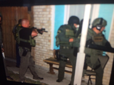 St. Bernard Sherif's deputies approach a house on Tara Drive in Violet at the beginning of a round- up of alleged drug dealers.