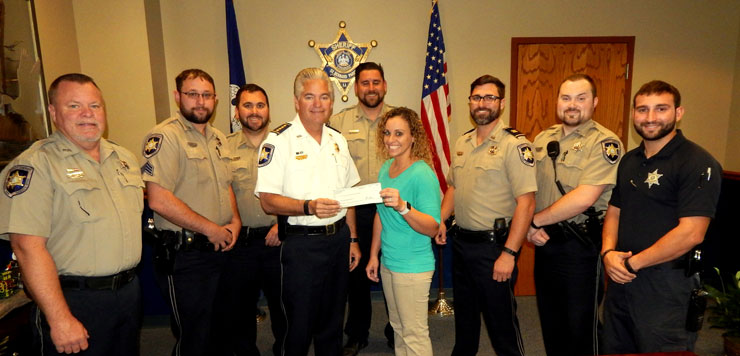 """Sheriff James Pohlmann presented a check for $2,350 to Jasmine Short of the American Cancer Society in New Orleans, on Nov. 30 and with them are seven deputies who were among 47 who pledged $50 each and took part in a """"Shaveless November'' to donate the money to the charity. The officers, from left, are Dep. Frank Auderer III, Sgt. Emile Breaux, Cpl. Jeff Babin, Sgt. Ryan Laylle, Capt. Justin Meyers, Dep. Robert Maloz and Dep. Richard Scheuermann."""
